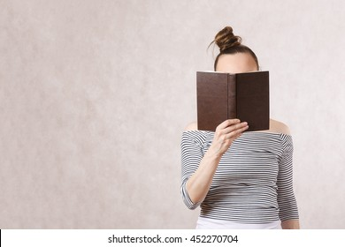 A young pretty woman between 30 and 40 years old with a book. Free space for a text