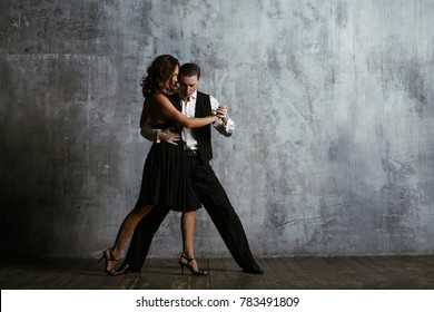 Young pretty woman in black dress and man dancing waltz.