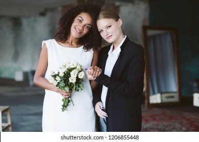 Young pretty woman with blond hair in black suit and beautiful african american woman with dark curly hair in white dress with little bouquet of flowers happily looking in camera on wedding ceremony