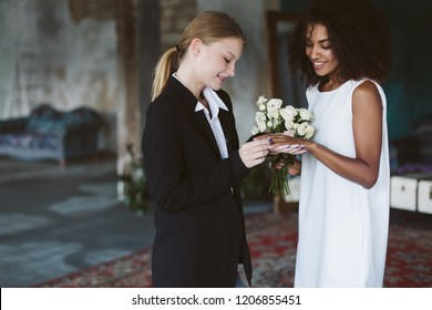 Young pretty woman with blond hair in black suit putting a wedding ring on beautiful african american woman with dark curly hair in white dress on wedding ceremony