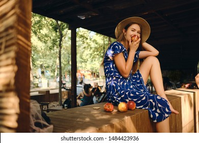 Young pretty woman in blue dress and hat barefoot eating peach joyfully looking in camera sitting on wooden fence in city park