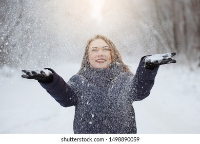 Young, pretty woman in a blue scarf and jacket with long hair throws up snowflakes in the fresh air in a snowy forest. Youth, beauty, healthy lifestyle, dreams.