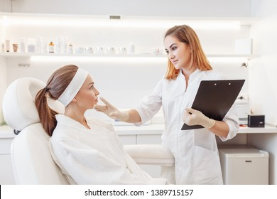 Young pretty woman came to a beauty salon and consults with a beautician on anti-aging treatments. Self care concept