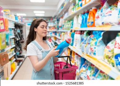 A young pretty woman chooses a cleaning agent in the store. Purchase and sale of goods in the store. Close up