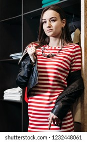 78559f69b068 The young pretty woman choosing, trying and buys dresses at shop clothing.  Banner for