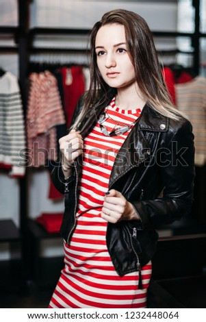 9bdde9f29079 The young pretty woman choosing, trying and buys dresses at shop clothing.  Banner for online store clothing. Girl posing in fashionable clothes - Image