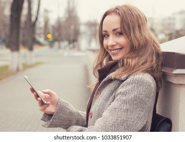Young pretty woman in coat sitting on street with phone in hands and smiling at camera.