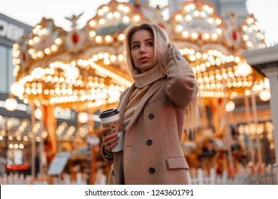 Young pretty woman in a coat and a vintage knitted sweater holds a cup of coffee and walks in an amusement park on the background of a carousel in the city. Elegant cute girl.