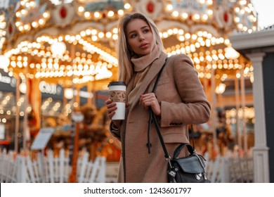 Young pretty woman in a coat and a vintage knitted sweater with black bag holds coffee walks in an amusement park on the background of a carousel decorated with festive garland in the city