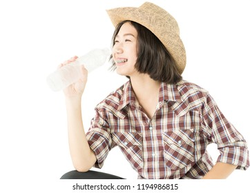 Young pretty woman in a cowboy hat and plaid shirt holding a water bottle isolated on white background