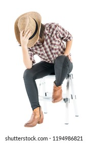 Young pretty woman in a cowboy hat and plaid shirt with hand on her hat isolated on white background