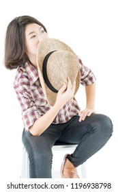 Young pretty woman in a cowboy hat and plaid shirt posing in studio with isolated on white background