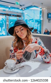 Young pretty woman crocheting with gray cotton yarn in a coffe shop, handmade crochet hobby project, drinking coffee