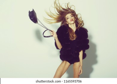 young pretty woman or cute sexy girl with long beautiful curly blonde hair and adorable face in black fur vest or waistcoat holds fashionable bag with chain on white background, copy space