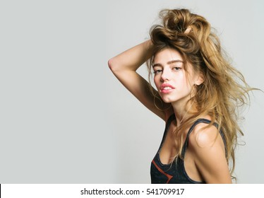 young pretty woman or cute sexy girl with long hair in fashionable vest, poses on grey background, copy space