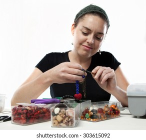 Young pretty woman doing bead work and making jewelery