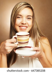 young pretty woman drinking coffee over beige background