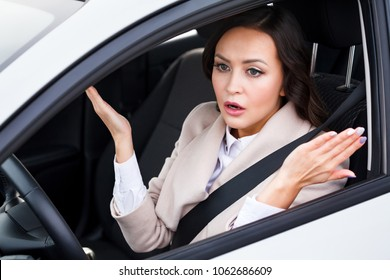 Young pretty woman driver driving a car and arguing with someone
