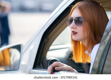 Young pretty woman driver in sunglasses looking out the car front window on a sunny summer day.