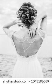 Young pretty woman in elegant dress. Back view fashion background. Monochrome.