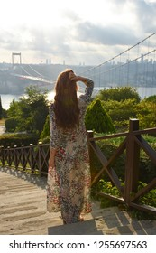 Young pretty woman enjoy of panoramic view of the Fatih Sultan Mehmet Bridge. Sunset time.Photo was taken from Otagtepe, Beykoz in Istanbul, Turkey.