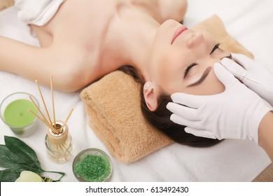 Young pretty woman enjoying face massage procedure