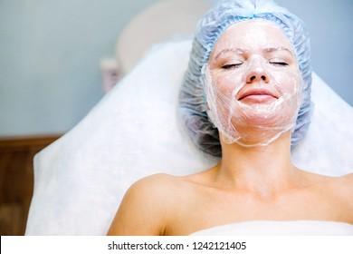 Young pretty woman enjoying a facial mask procedure