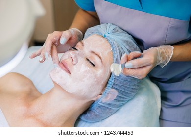 Young pretty woman enjoying a facial mask procedure