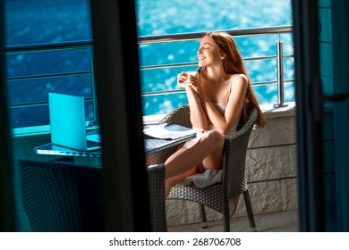 Young and pretty woman enjoying morning on the balcony near the sea.