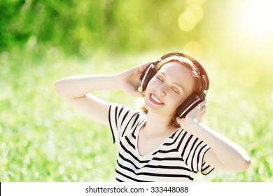 Young pretty woman enjoying music in headphones in summer park