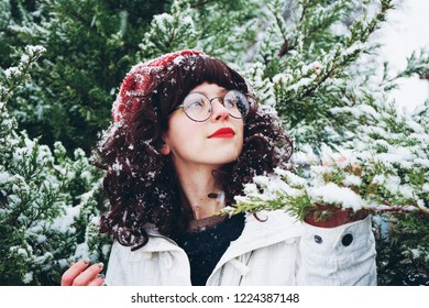 Young and pretty woman enjoying a snowy winter day surrounded by trees