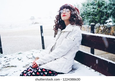 Young and pretty woman enjoying a snowy winter day
