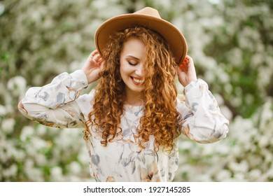 Young pretty woman enjoys standing near flowering spring tree. A girl wearing beige hat and white dress smiles among blooming apple trees. Spring season concept