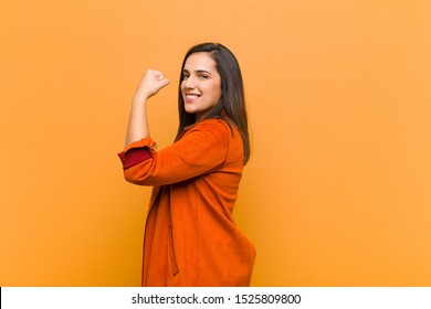 young pretty woman feeling happy, satisfied and powerful, flexing fit and muscular biceps, looking strong after the gym isolated against orange wall