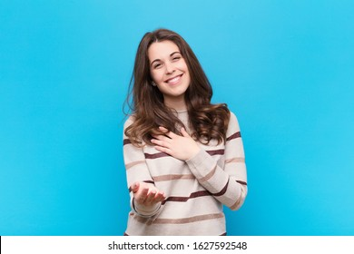 young pretty woman feeling happy and in love, smiling with one hand next to heart and the other stretched up front against blue wall