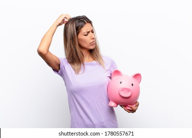 young pretty woman feeling puzzled and confused, scratching head and looking to the side with a piggy bank.
