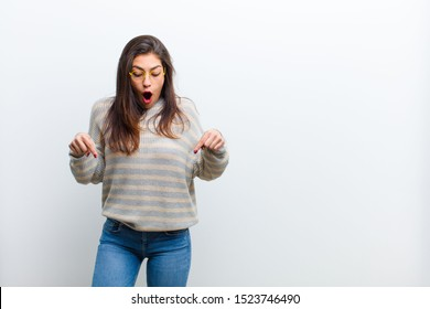 young pretty woman feeling shocked, open-mouthed and amazed, looking and pointing downwards in disbelief and surprise isolated against white wall