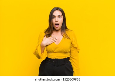 young pretty woman feeling shocked, astonished and surprised, with hand on chest and open mouth, saying who, me? isolated against orange wall