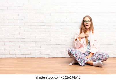 young pretty woman feeling shocked, astonished and surprised, with hand on chest and open mouth, saying who, me? . home concept