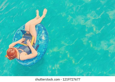 Young pretty woman freelancer is floating on the sea or in the pool in a swimming circle. A girl is relaxing on the ocean or in the dug-out pool on the inflatable ring with laptop and copyspace