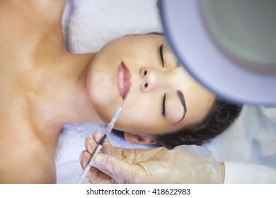 Young pretty woman getting cosmetic injection in the face like a part of the clinic treatment. Medicine, healthcare and beauty concept
