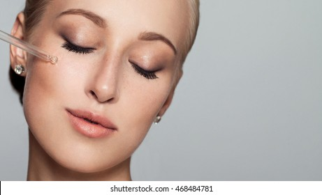 Young pretty Woman getting special skin treatment at beauty salon. Beautiful Girl applying eye serum. Closed eyes. Isolated on gray background. Smooth skin without wrinkles.