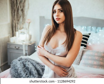 Young pretty woman in gray nightwear in her bed.