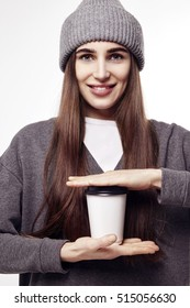 Young pretty woman in a grey clothes holds a coffee paper cup. Takeaway package for layout.