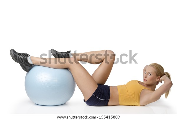young pretty woman with gym body , doing stretching exercise with ball isolated on white looking in camera