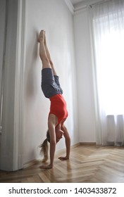 Young pretty woman handstanding at a wall.