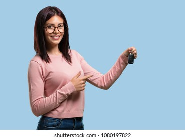 Young pretty woman happy and smiling, holding the keys of the car, confident, offering them to start your new car