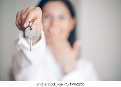 Young pretty woman happy and smiling, holding the keys of the car