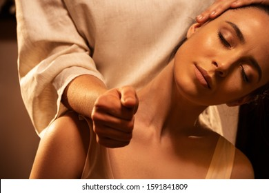 Young pretty woman has Thai massage. Close up of neck stretching. Concept of serene spa treatments.