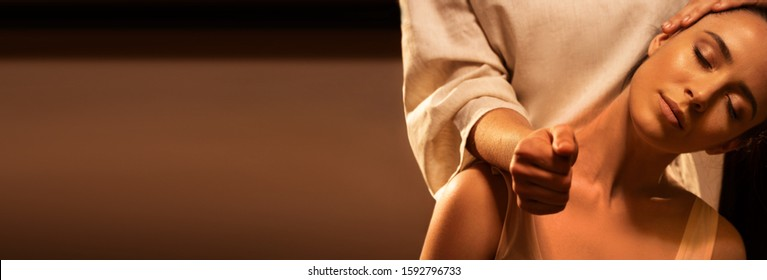 Young pretty woman has Thai massage. Close up of neck stretching. Warm inviting colors, calm atmosphere, charming light. Concept of serene spa treatments. Extended background for design.